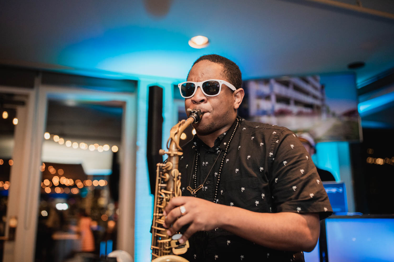 African-American man in sunglasses and black-and-white polka dot shirt plays the saxophone.