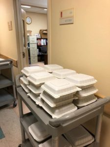 Cart of takeout containers of meals.
